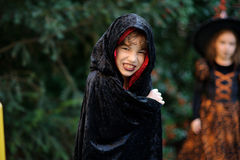 Junge des jüngeren schulpflichtigen Alters in einem schwarz-roten Mantel schildert den schlechten Zauberer Stockfotografie