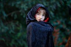 Junge des jüngeren schulpflichtigen Alters in einem schwarz-roten Mantel schildert den schlechten Zauberer Stockfoto