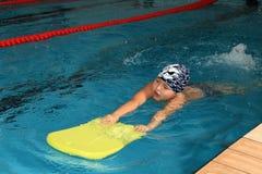 Junge des schulpflichtigen Alters, ungefähr 8 Jahre alt, lernend zu schwimmen. Lizenzfreie Stockfotos