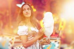 Junge Deutsche, die einen Dirndl trägt und Candyfloss isst Lizenzfreie Stockfotos