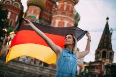 Junge Deutsche in Russland Deutscher, der eine Flagge wellenartig bewegt stockfoto