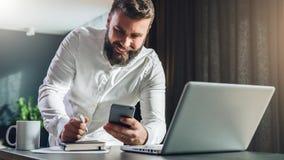 Junge, die den bärtigen Geschäftsmann steht nahe Tabelle vor Laptop, unter Verwendung des Smartphone smilling sind Mann überprüft Stockfotografie