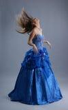 Junge, die in einem blauen Kleid blond sind, rütteln ihr Haar Stockbild