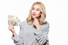 Junge, die hübsche Frau in der grauen Strickjacke hält das Bündel Eurobanknoten, aufwärts schauend mit der Hand auf dem Kinn denk stockfotos