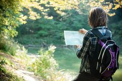 Junge die Karte betrachtende und beim Wandern steuernde Frau durch Wald lizenzfreies stockbild