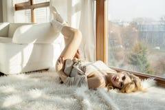 Junge dünne sexy Frau in der braunen Strickjacke gegen das Fenster Lizenzfreies Stockfoto