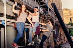 Junge drei Freunde, die Spaß auf Bauzone in der Stadt haben Stockfotografie