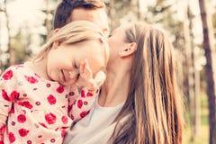 Junge dreiköpfige Familie, die Spaß in einem Park zusammen genießt ihre Zeit hat Wirkliche Leute, Echtheitskonzept lizenzfreies stockfoto