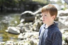 Junge durch den Flussufer Stockfoto