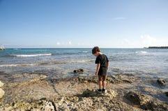 Junge durch den Ozean Stockbild