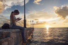 Junge durchdachte Frauen sitzt allein auf einem Pier und schreibt sms Lizenzfreies Stockfoto
