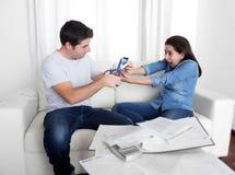 Junge Ehemannausschnittkreditkarte mit der Scherenfrau, die versucht, ihn zu stoppen stockbild