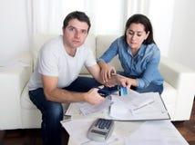 Junge Ehemannausschnittkreditkarte mit der Scherenfrau, die versucht, ihn zu stoppen lizenzfreie stockfotografie