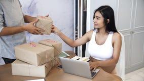 Junge Ehemannhilfe seine schwangere Frau, die zu Hause arbeitet Lizenzfreie Stockfotos