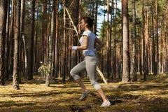 Junge Eignungsfrau, die über Klotz während auf extremem Eignungstraining im Freien im Wald läuft und springt lizenzfreie stockfotos