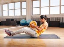 Junge Eignungsfrau, die in der Turnhalle trainiert Stockfotos
