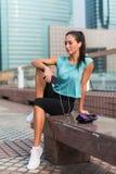 Junge Eignungsfrau, die nachdem dem Trainieren, sitzend an der Bank im Stadtzentrum stillsteht lizenzfreie stockfotos