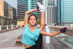 Junge Eignungsfrau, die stehende aufgeteilte Übung auf der Stadtstraße tut Sportliches Sitzmädchen, das draußen ausdehnen ausarbe stockbild