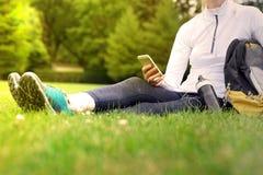 Junge Eignungsfrau mit dem Handy, der einen Rest hat Stockfoto