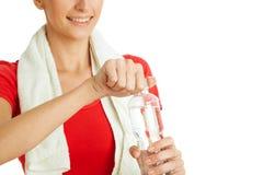 Junge Eignungsfrauen-Öffnungsflasche Wasser Stockbild