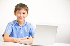 Junge in einem blauen Hemd benutzt einen Laptop, der zuhause an einem Tisch sitzt lizenzfreie stockbilder