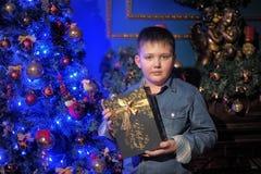 Junge in einem Denimhemd mit einem Geschenk in den Händen Lizenzfreie Stockbilder