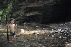 Junge in einem Dschungel mit einem Palmblatt Lizenzfreie Stockfotografie