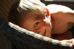 Junge in einem geflochtenen Stuhl Lizenzfreie Stockfotografie