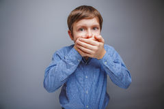 Junge in einem Hemd bedeckte Schreckenmund mit ihren Händen lizenzfreies stockfoto