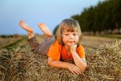 Junge in einem Heuschober auf dem Gebiet Lizenzfreie Stockfotos