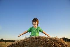 Junge in einem Heuschober auf dem Gebiet Stockfoto