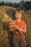 Junge in einem Heuschober auf dem Gebiet Lizenzfreie Stockfotografie