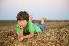 Junge in einem Heuschober auf dem Gebiet Lizenzfreies Stockfoto