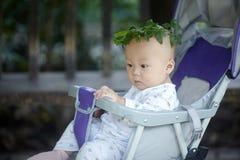 Junge in einem Kranz von Blättern Stockfotos