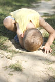 Junge in einem Loch Stockbild