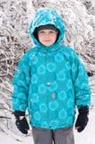 Junge in einem schneebedeckten Wald lizenzfreies stockfoto