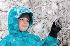 Junge in einem schneebedeckten Wald stockbild