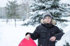 Junge in einem schneebedeckten Wald mit Schlitten stockfotos