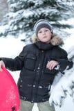 Junge in einem schneebedeckten Wald mit Schlitten stockfotografie