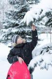 Junge in einem schneebedeckten Wald mit Schlitten lizenzfreies stockfoto