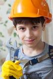 Junge in einem Schutzhelm und mit einem wrenc Lizenzfreies Stockbild