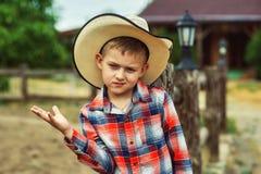 Junge in einem Strohhut in der Landschaft stockbild