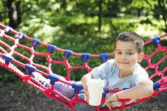 Junge in einer Hängematte mit einer Papierschale des Getränks lizenzfreie stockbilder