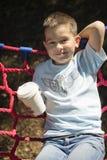 Junge in einer Hängematte mit einer Papierschale des Getränks stockfotografie