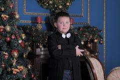 Junge in einer Klage gegen den Hintergrund des Weihnachtsbaums stockbilder