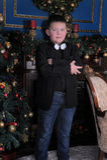 Junge in einer Klage gegen den Hintergrund des Weihnachtsbaums stockfotografie