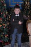 Junge in einer Klage gegen den Hintergrund des Weihnachtsbaums lizenzfreie stockfotografie