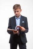 Junge in einer Klage mit einem Notizbuch in der Hand Stockbilder