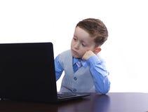 Junge in einer Klage und in einem Laptop Lizenzfreie Stockfotos