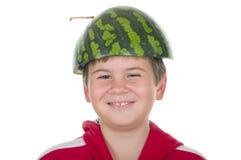 Junge in einer Schutzkappe von einer Wassermelone Lizenzfreies Stockfoto